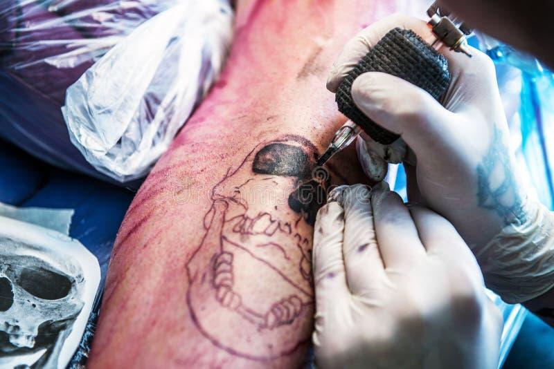 Making a Skull Tattoo. Making Classic Skull Tattoo on the Arm. Tattoo Making Closeup royalty free stock images