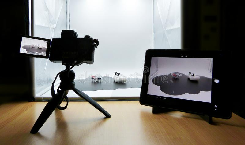 Making a studio shot using a light box. Camera on tripod, tablet set on camera remote control royalty free stock photography