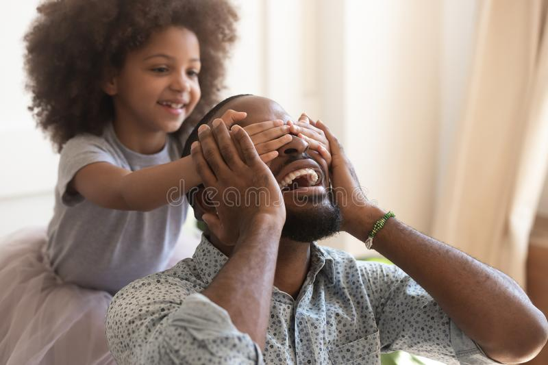 Cute african kid daughter close eyes making surprise for daddy stock photos