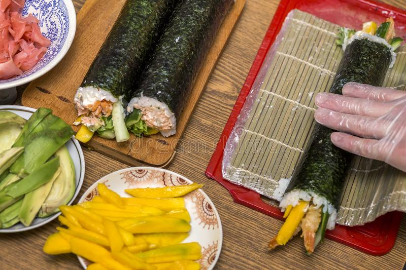 Making sushi and rolls at home. Plates with ingredients for traditional Japanese food and sushi rolls on wooden board on kitchen. Table, view from above royalty free stock photo