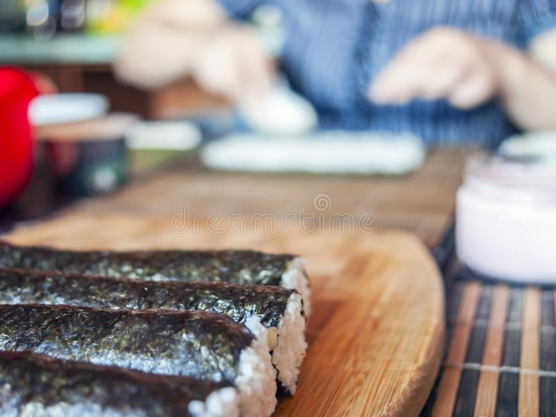 Making Sushi Rolls: Rolls Sealing On the Wooden Board before Slicing. Blurred Woman Hands Putting Rice on a Nori Sheet and royalty free stock images