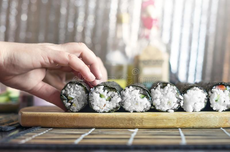 Making Sushi Rolls Workshop. Female Hands Put Rolls On the Wooden Board for Sealing. Kitchenware and Shiny Metal Background stock images