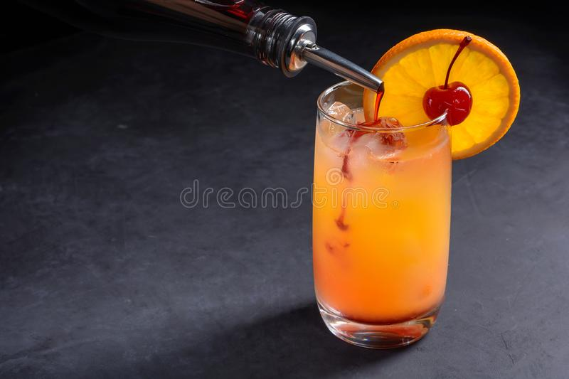 Making Tequila Sunrise Cocktail. Grenadine slowly poured into a glass of ice, orange juice and tequila. Dark stone background with. Making Tequila Sunrise royalty free stock photography