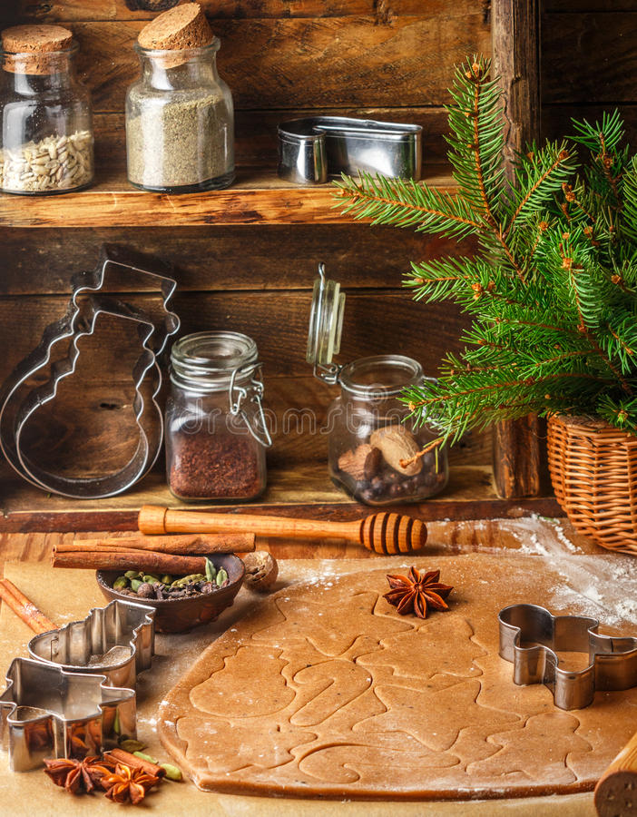 Making traditional gingerbread. Christmas. New year. Raw dough, cutting cookie and condiments on the table. Anise, cloves, cardamom, cinnamon. Rustic style stock photography
