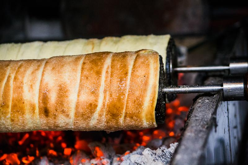 Making of traditional Kurtos Kalacs over burning charcoal. Kürtőskalács is a spit cake specific to Hungary and Hungarian-speaking regions in Romania royalty free stock photography