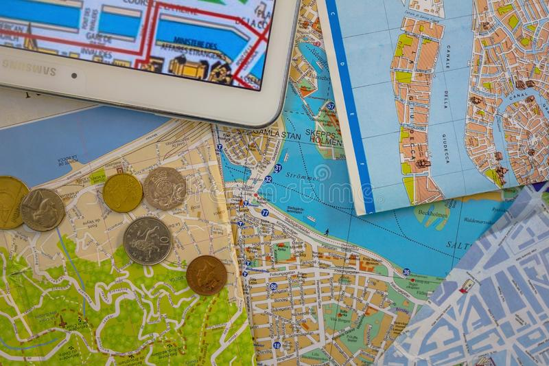 Making a travel plan. Several maps of European cities. The streets and sights are indicated. On top of small money. Bright background of blue, green and brown royalty free stock photo