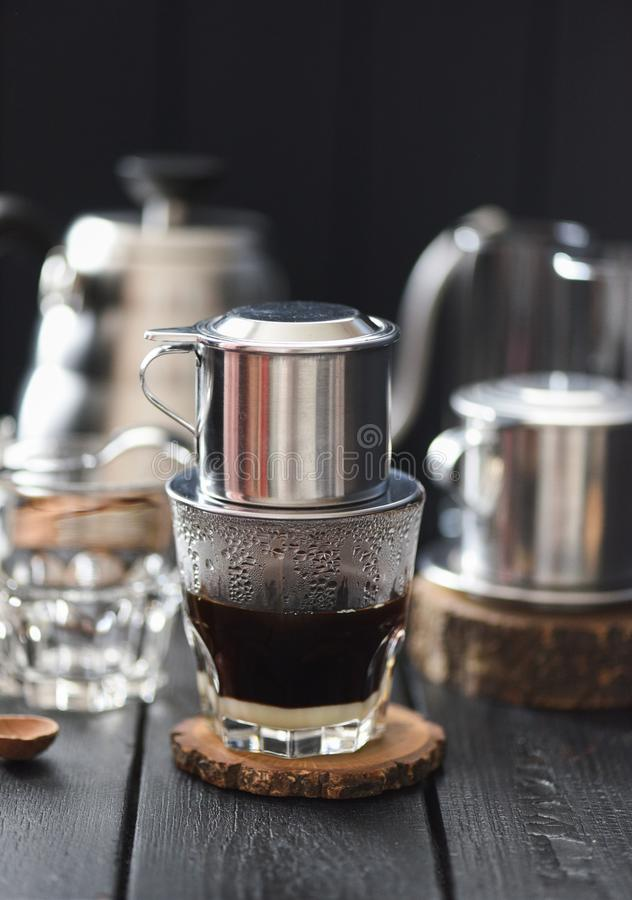 Making Vietnamese black drip coffee in phin on black background stock images