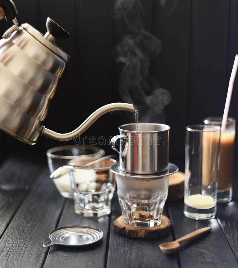 Free Making Vietnamese Drip Coffee. Pouring Steaming Hot Water Into Phin From Goose Neck Kettle On Black Background Stock Photography - 154211812