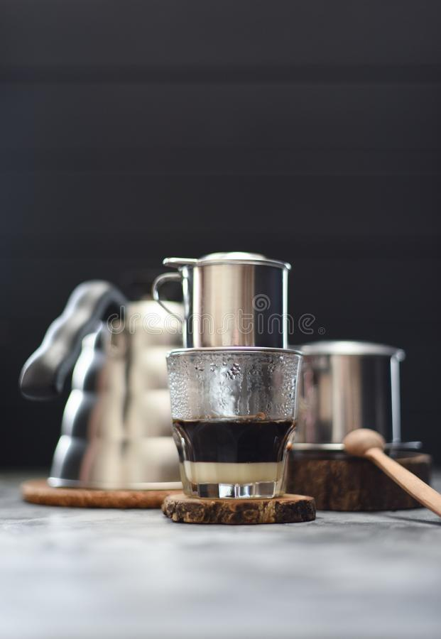 Making Vietnamese drip coffee. Traditional Vietnamese coffee maker phin and goose neck kettle on dark background copy space stock photography