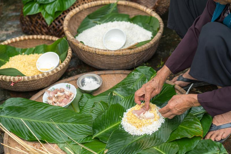 Making wrapping Chung Cake, the Vietnamese lunar new year Tet food outdoor with old woman hands and ingredients. Closed-up. stock images