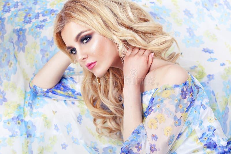 Makiyad och hår för härlig stående för flickamodellkvinna klär yrkesmässig i en blomma på en blom- bakgrund, den ljusa signalen,  royaltyfria bilder