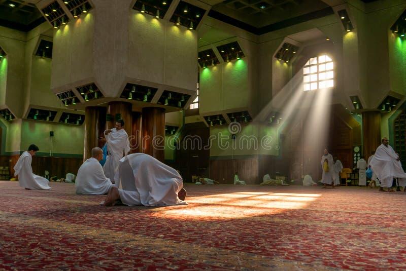 MAKKAH, ARÁBIA SAUDITA - CIRCA DEC 2016 : Peregrinos muçulmanos em roupas de ihram rezam na mesquita Tanaeem, a 7 km de Meca `Ihr fotografia de stock royalty free