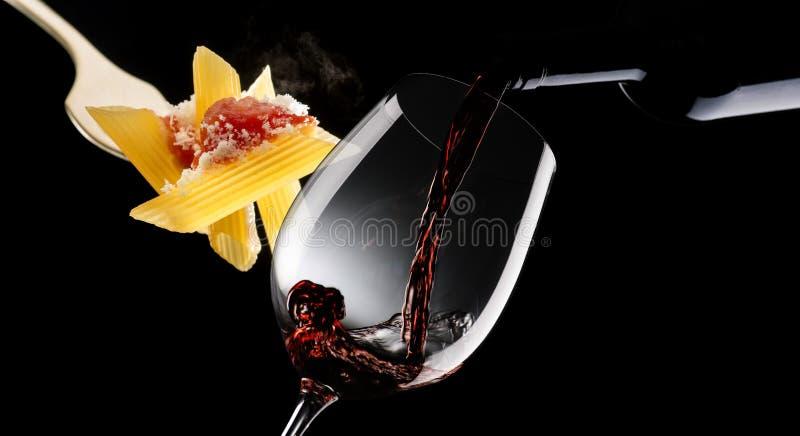 Makkaroni mit Tomatensauce und Glas mit Rotwein stockbilder