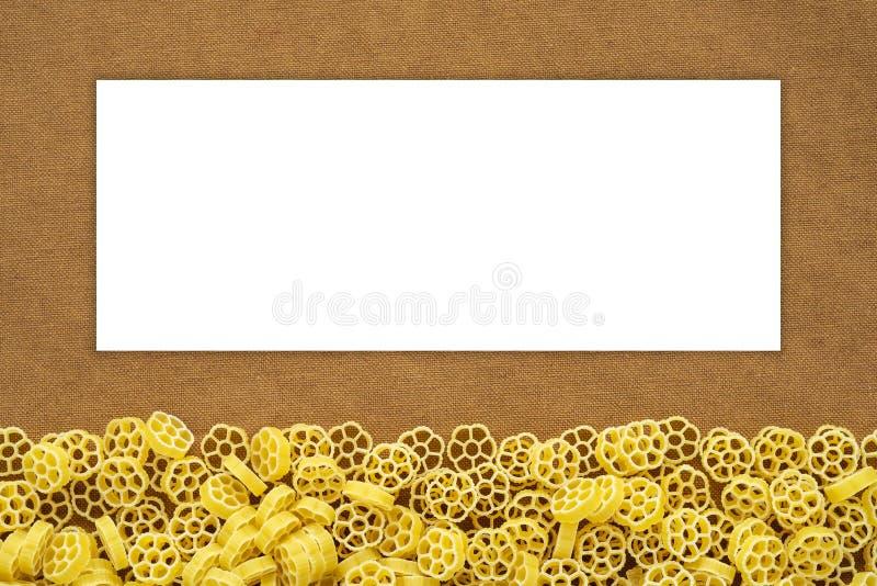 Makkaroni ruote schöne zerlegte Teigwaren von der Unterseite auf einem rustikalen braunen strukturierten Hintergrund Großaufnahme lizenzfreies stockfoto
