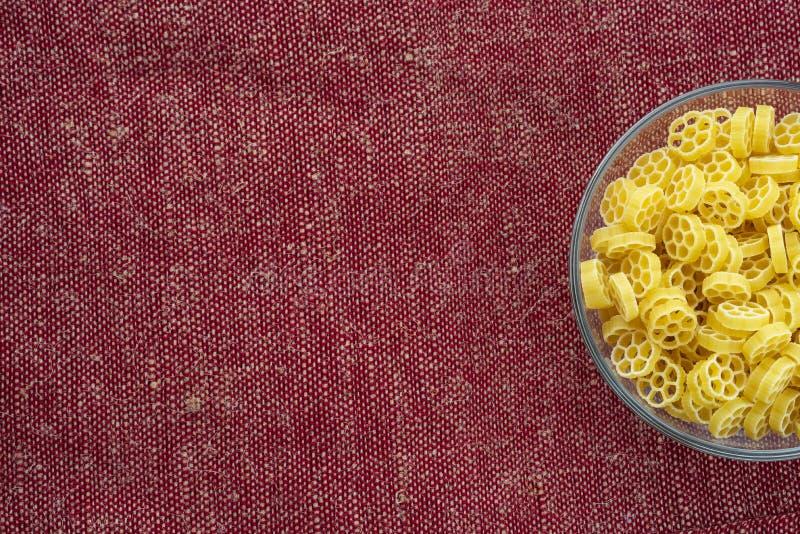 Makkaroni ruote Teigwaren in einer Glasschüssel auf einer rotbraunen rustikalen Hintergrundbeschaffenheit mit einer Seite Nahaufn lizenzfreies stockbild