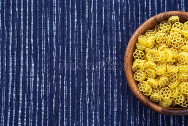 Makkaroni ruote Teigwaren in einer hölzernen Schüssel auf einem gestreiften weißen blauen Stoffhintergrund mit einer Seite Nahauf stockbild