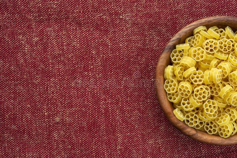 Makkaroni ruote Teigwaren in einer hölzernen Schüssel auf einem rotbraunen rustikalen Beschaffenheitshintergrund mit einer Seite  stockfotos