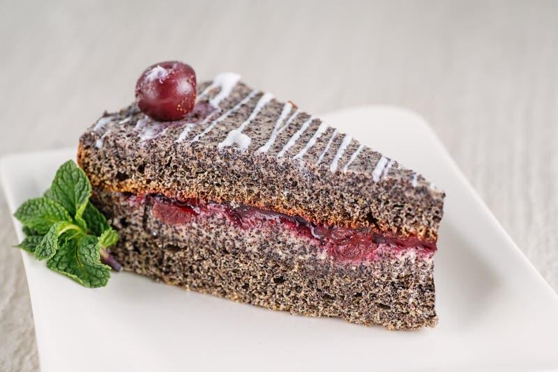 Makowy śmietanka tort z białą wiśnią na wierzchołku i polewą, produkt fotografia dla patisserie zdjęcia royalty free