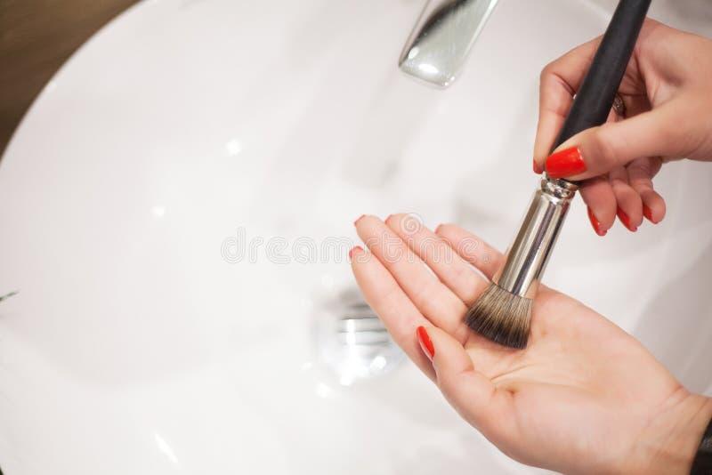 Makr επάνω στη βούρτσα Γυναίκα που πλένει τη βρώμικη βούρτσα makeup με το σαπούνι και τον αφρό στο νεροχύτη στοκ φωτογραφία με δικαίωμα ελεύθερης χρήσης