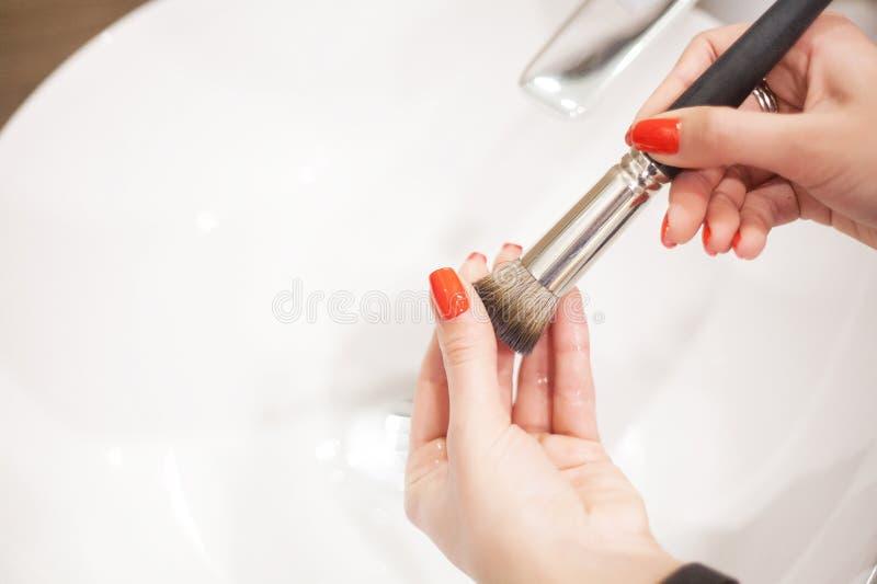 Makr επάνω στη βούρτσα Γυναίκα που πλένει τη βρώμικη βούρτσα makeup με το σαπούνι και τον αφρό στο νεροχύτη στοκ εικόνες με δικαίωμα ελεύθερης χρήσης