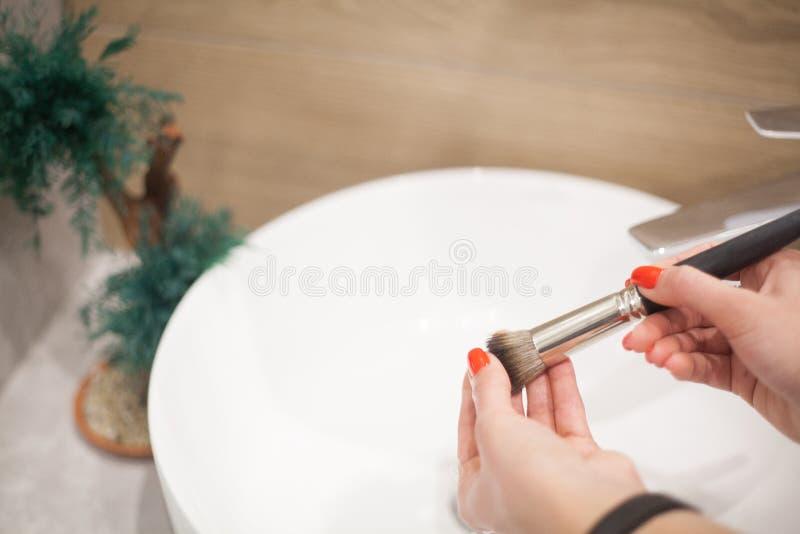 Makr επάνω στη βούρτσα Γυναίκα που πλένει τη βρώμικη βούρτσα makeup με το σαπούνι και τον αφρό στο νεροχύτη στοκ φωτογραφίες
