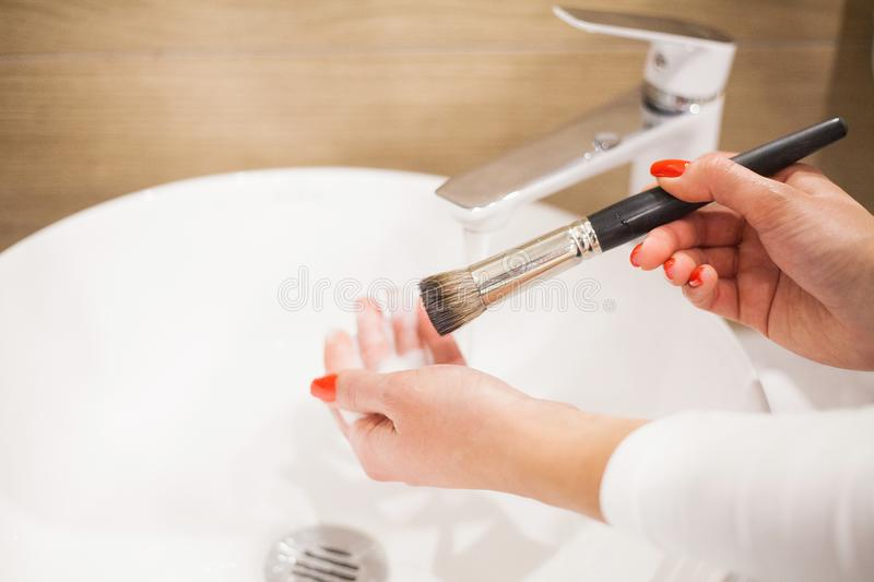 Makr up brush. Woman washing dirty makeup brush with soap and foam in the sink.  royalty free stock images