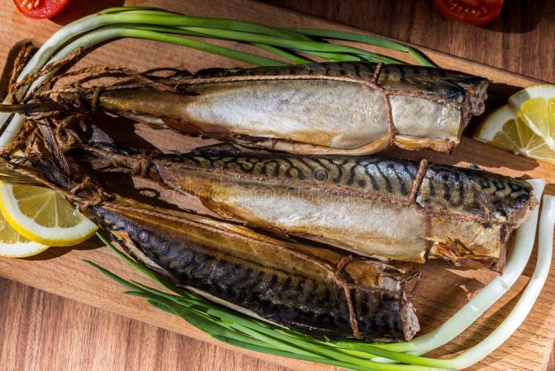 Makreel gerookte vissen op houten houtvezelplaat op houten lijst stock fotografie