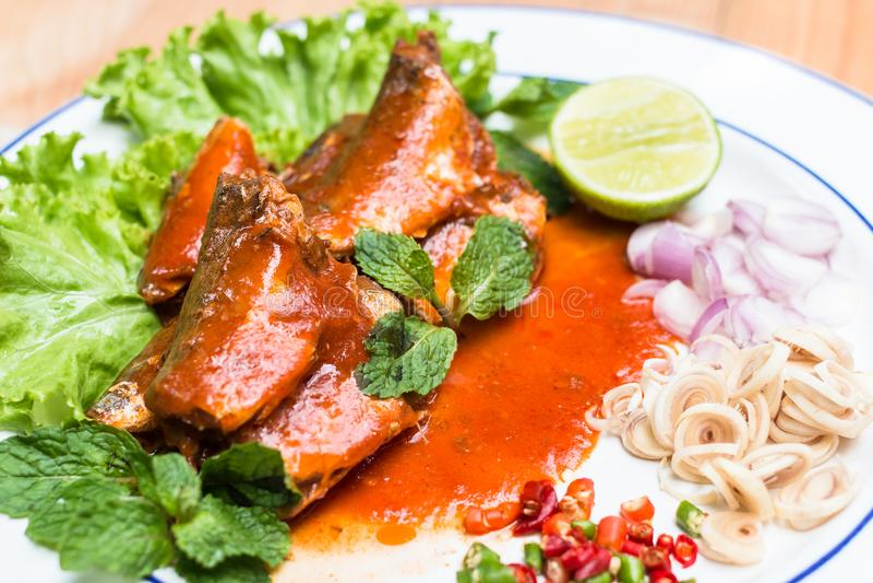 Makrelenfische in der Tomatensauce und dem Koch im thailändischen würzigen Salat stockfotografie