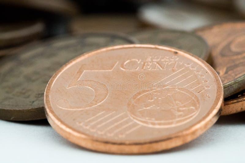 Makro av ett mynt f?r cent f?r euro som fem st?ttas p? mer bronsmynt Vit bakgrund arkivbilder