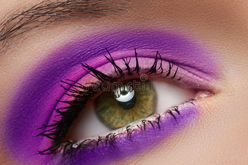 Makro av kvinnligögat med det violetta modesminket royaltyfri fotografi