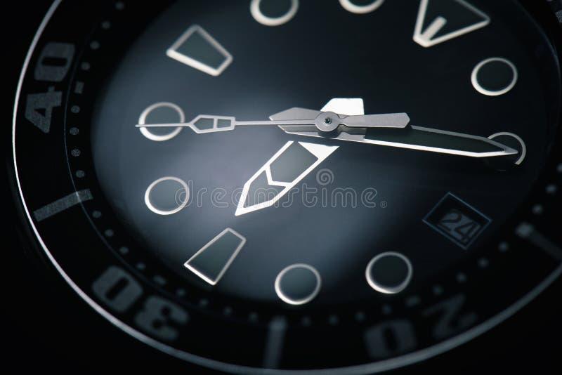Makro- czarny zegarek z srebnymi zegarowymi rękami fotografia stock