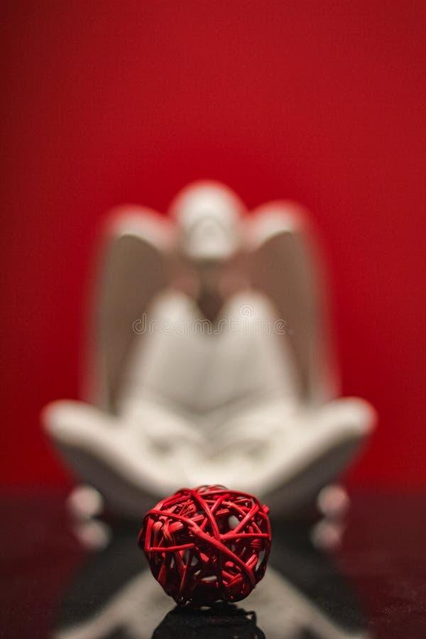 Makro de boule rouge de paille avec l'ange blanc brouillé à l'arrière-plan image stock