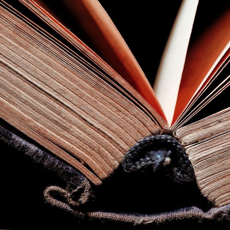 Makro des offenen Buches auf dem schwarzen Hintergrund stockfotografie