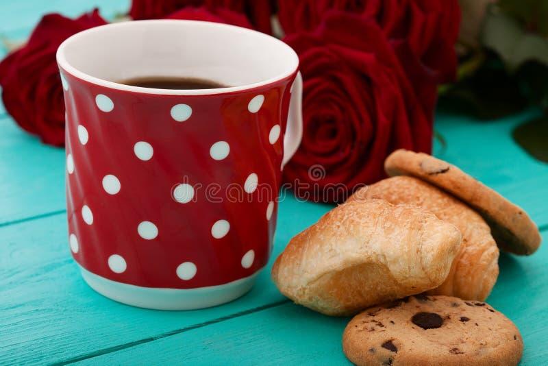 Makro- filiżanka kawy z croissants i kwiat różami na błękitnym drewnianym stole Selekcyjna ostrość obraz royalty free