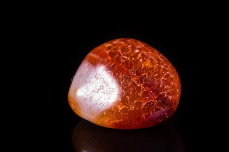 Makro- kopalina kamienia pomarańczowy onyks na czarnym tle zdjęcia stock