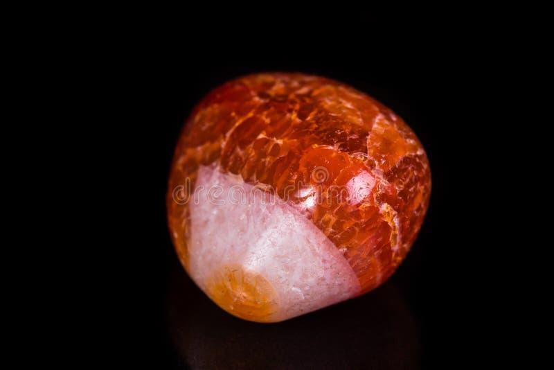 Makro- kopalina kamienia pomarańczowy onyks na czarnym tle fotografia royalty free