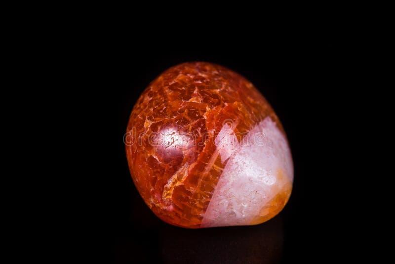 Makro- kopalina kamienia pomarańczowy onyks na czarnym tle obraz stock