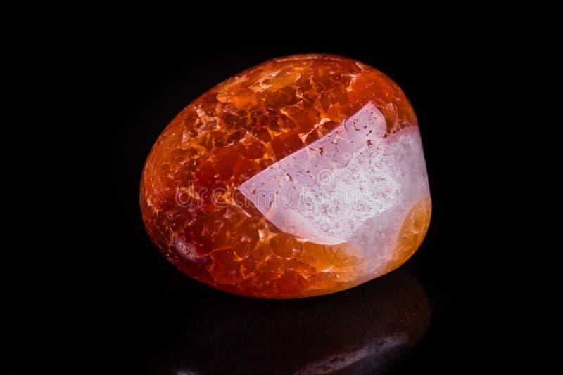 Makro- kopalina kamienia pomarańczowy onyks na czarnym tle zdjęcia royalty free