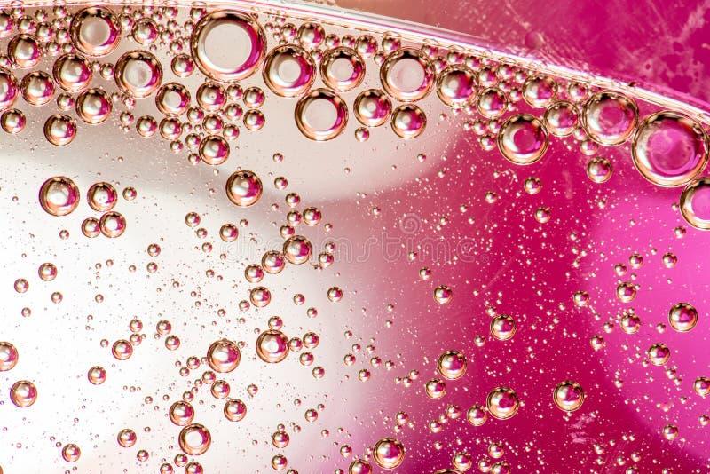 Makro- strzał backlit ciecz z małymi bąblami w nim nad barwionym tłem zdjęcie royalty free