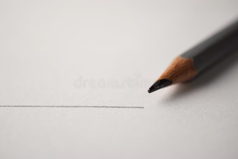 Makro- strzał czarny ołówkowy grafit z rysunek linią na textured białej księdze obraz stock