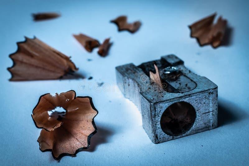 Makro- szczegółu zbliżenie używać popielatego metalu ołówkowa ostrzarka z drewnianymi zawijasów goleniami od ostrzyć ołówek na bi obraz royalty free