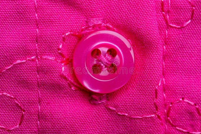 Makro zdjęcie przyszytego różowego guzika na różowej tkance z haftem Szczegółowe informacje o ubraniu dziewczynki zdjęcie royalty free