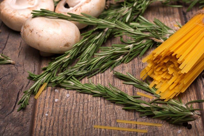 Makrobild av gula okokta nudlar, champinjoner och rosmarinris Okokta ingredienser på en trätabell royaltyfri bild