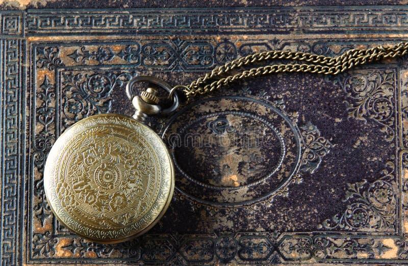 Makrobild der alten Weinlesetaschenuhr auf altem Buch Beschneidungspfad eingeschlossen lizenzfreie stockfotografie