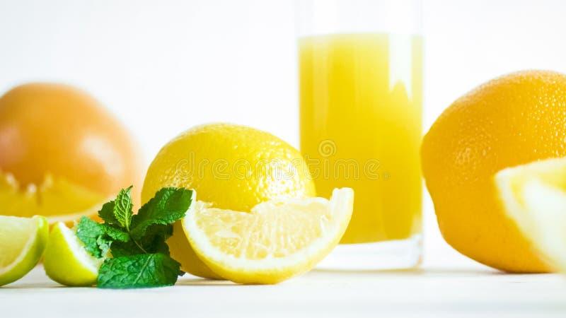 Makrobild von Zitrusfrüchten, von tadellosen Blättern und von Glas Orangensaft auf weißem backgorund lizenzfreie stockfotografie