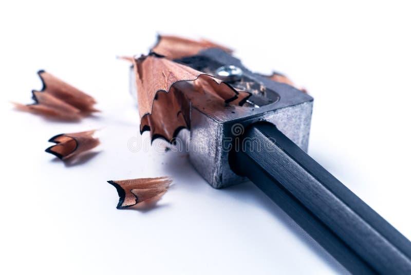 Makrocloseup av att vässa en blyertspenna med en grå metallvässare med trävirvelshavings på vit bakgrund arkivfoto