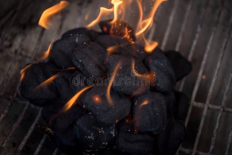 Makrocloseup av flammor på kol i grillfestgrop royaltyfri foto
