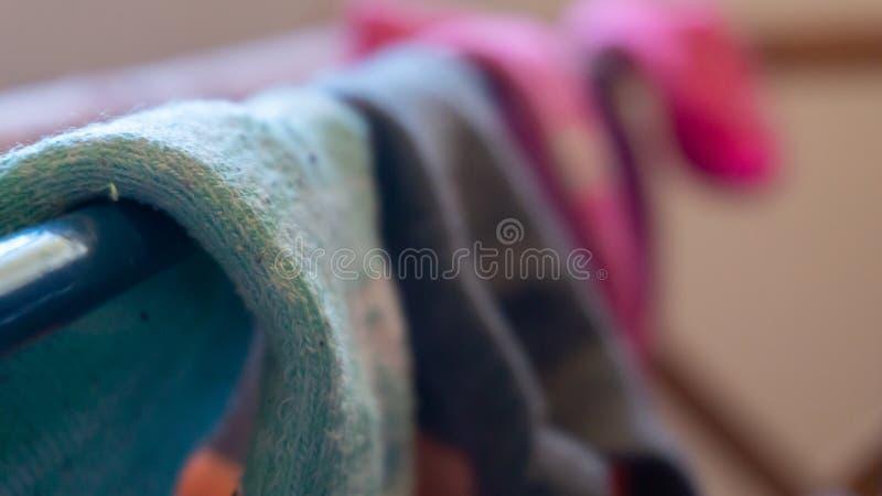 Makrodetalj av det vävde ankelsockaslutet upp som torkar på en tvätterikugge, med suddig bakgrund av andra sockor som matchas dål royaltyfri fotografi