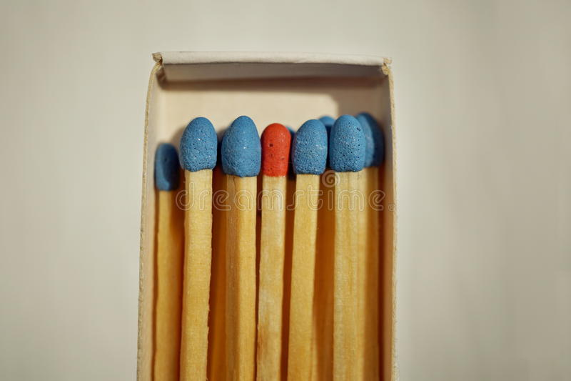 Makrodetalj av en ask av matchtändsticksasken mycket av matcher med blåttöverkanten och en som är olik med en röd överkant arkivfoto