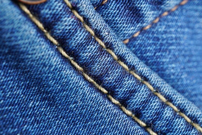Makrodetalj av en gul tråd som syr typisk blå jeans för man` s royaltyfria foton